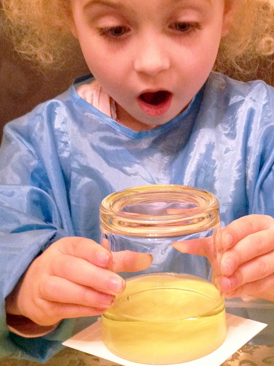 Amazed girl holding an inverted glass of coloured water