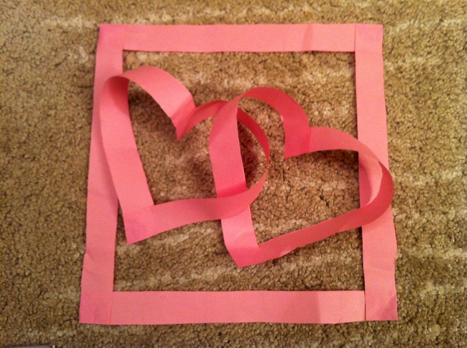 Two interlocking paper hearts within a paper square